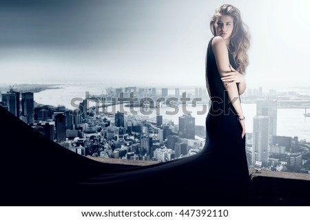 Stylish beautiful woman posing in black elegant dress. Skyline on background. - stock photo