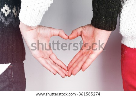 Stylish beautiful young couple in love with heart shaped hands, celebrating Valentine's Day - stock photo