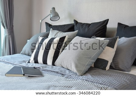 stylish bedroom interior design with black patterned pillows on bed and decorative table lamp