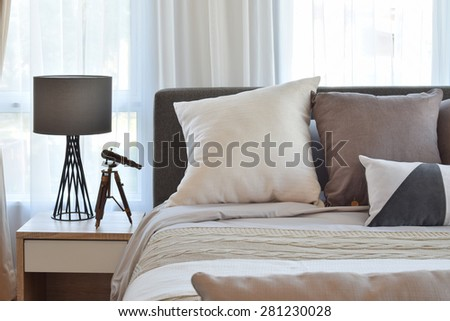 stylish bedroom interior design with brown patterned pillows on bed and decorative table lamp. - stock photo