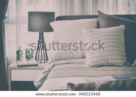 stylish bedroom interior design with brown patterned pillows on bed and decorative table lamp with vintage style effect - stock photo