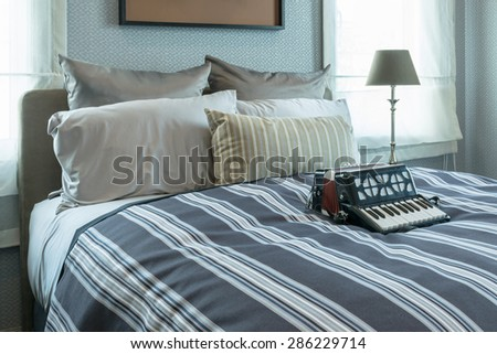stylish bedroom interior design with striped pillows and decorative accordion on bed  - stock photo