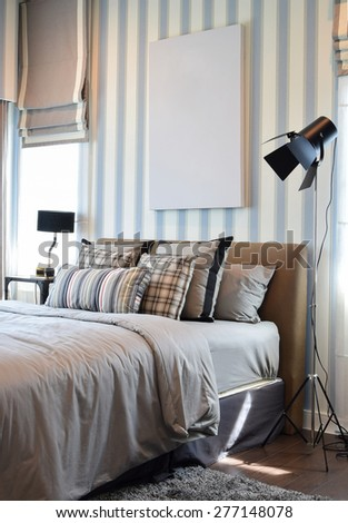 stylish bedroom interior design with striped pillows on bed and decorative table lamp. - stock photo
