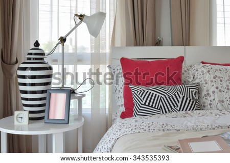 stylish bedroom interior with flower pattern pillows and decorative table lamp