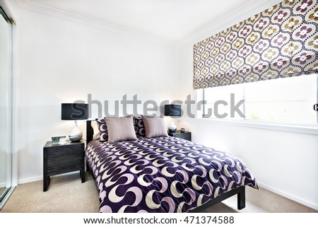 Stylish bedroom with abstract designs and sunlight through the window into the room which included attractive pattern art on the bed sheet with pillows among the lamps