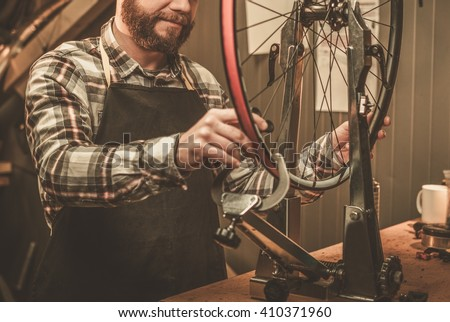 Stylish bicycle mechanic doing his professional work in workshop. - stock photo