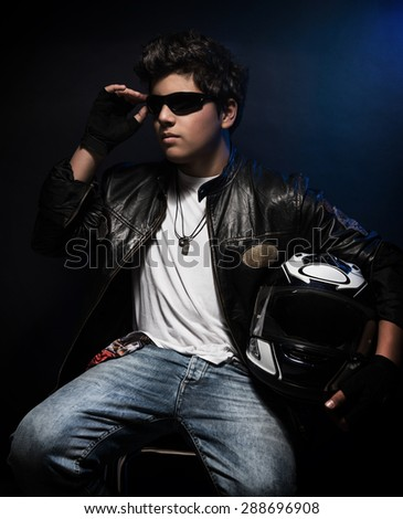 Stylish biker guy sitting on chair with helmet in hand over dark blue background, active lifestyle, professional motorcyclist, fashion for youth