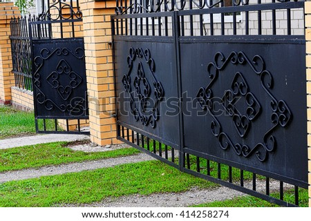 Stylish black gate with brick column at cottage