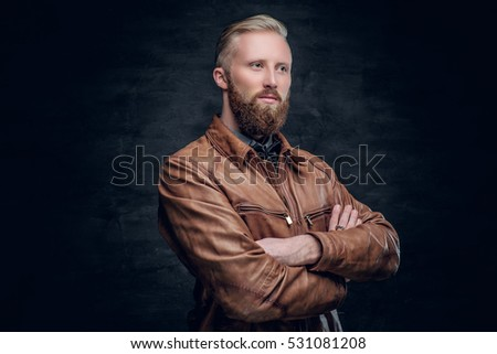 Stylish blond, bearded male with crossed arms, dressed in a brown leather pilot jacket.