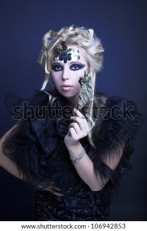 Stylish blond woman in dark dress with furs and with dry leaf in her hand