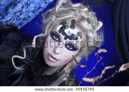 Stylish blond woman in dark dress with furs and with dry twig