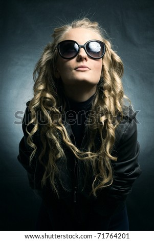 Stylish blonde in sunglasses on a dark background. - stock photo