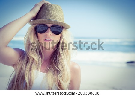 Stylish blonde looking at camera on the beach on a sunny day - stock photo