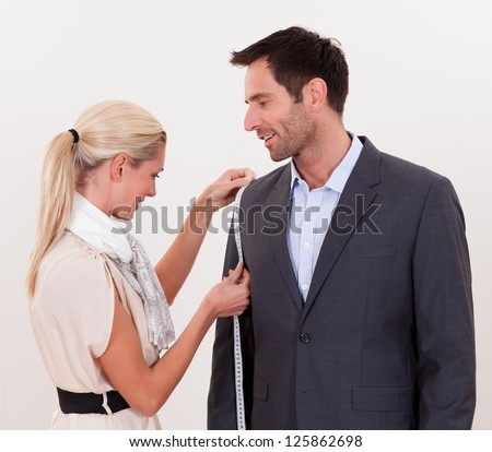 Stylish blonde seamstress measuring a businessman for a suit or in order to alter the one he is wearing - stock photo