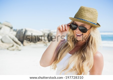 Stylish blonde smiling at camera on the beach on a sunny day - stock photo