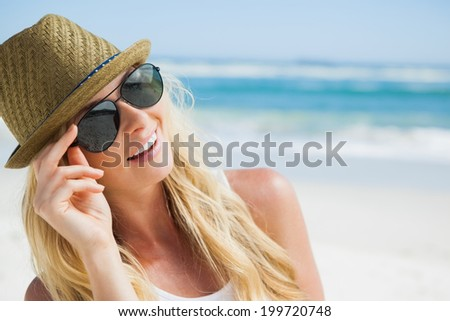 Stylish blonde smiling on the beach on a sunny day