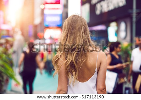 Stylish blonde woman walking outdoors in summer city street at sunset time wearing white dress with naked back. View from the back.