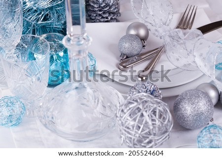 Stylish blue and silver Christmas table setting with a pretty translucent bow on white dinnerware with silver cutlery, pine cones and baubles, high angle close up view - stock photo