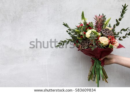 Stylish bouquet of brassica cabbage, pineapple decorative, eucalyptus and dried lotus with space for text