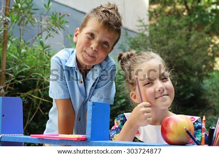 Stylish boy and girl playing school outside. Education and kids fashion concept.Fine art image