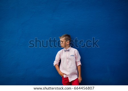 stylish boy in a pink shirt with a bow tie posing on blue background