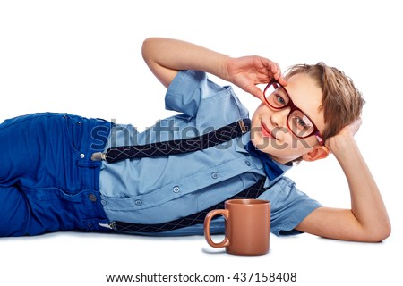 Stylish boy in glasses lying on the floor with cup of tea, coffee or juice. He is smiling and looking into the camera. Isolated on a white background. - stock photo