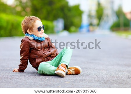 stylish boy in leather jacket posing on the ground - stock photo