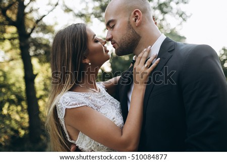 Stylish bride and bearded muscular groom posing on the wedding