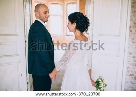 Stylish bride and groom  holding hands in a room with white brick. Loft