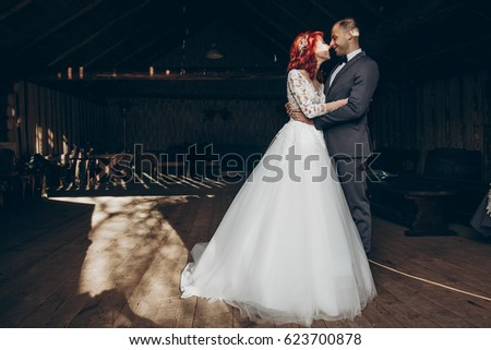 stylish bride and groom hugging in light on background of wooden wall in barn. rustic wedding concept, space for text. happy bohemian newlyweds, family couple embracing