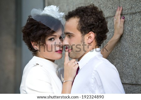 Stylish bride passionately presses the groom against the wall. Wedding. - stock photo