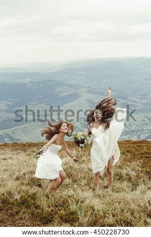stylish bridesmaid and gorgeous bride having fun and jumping, boho wedding, luxury ceremony at mountains - stock photo