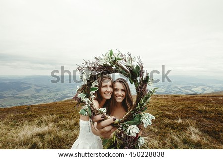 stylish bridesmaid and gorgeous bride laughing and looking through wreath, boho wedding, luxury ceremony at mountains - stock photo