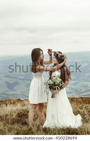 stylish bridesmaid helping gorgeous bride preparing, boho wedding, luxury ceremony at mountains - stock photo