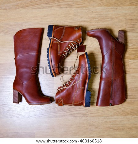 Stylish brown leather man and woman boots in vintage style on wooden background. Fashionable male and female leather autumn shoes with laces and heels. Fashion trend, family look concept. Flat lay. - stock photo