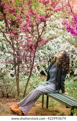 stylish brunette girl walks in the park with blooming flowers, spring season