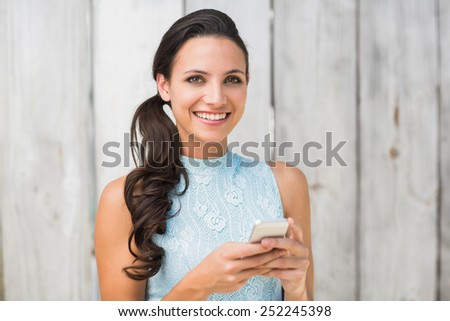Stylish brunette on the phone against bleached wooden fence - stock photo