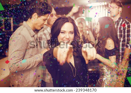 Stylish brunette smiling and dancing against flying colours - stock photo