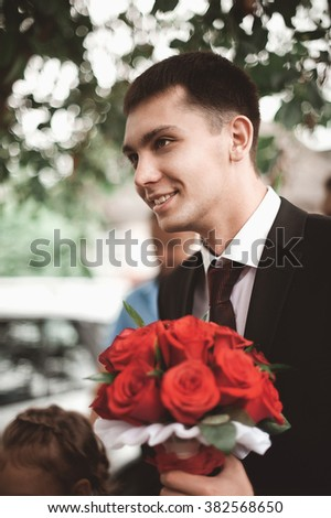 stylish brunette smiling groom in a suit  holds a luxurious bouquet of flowers