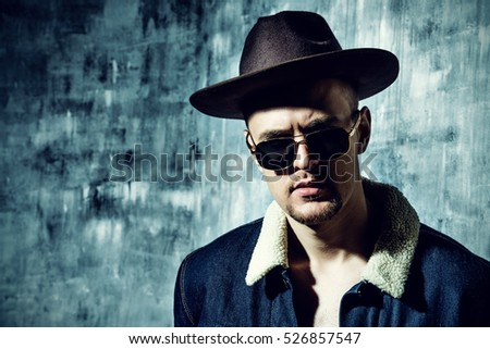 Stylish brutal man wearing jeans clothes and sunglasses posing over grunge background. Denim collection. Male fashion.