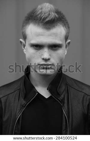 Stylish bully concept. Portrait of brutal young man with short hair wearing black jacket and posing over urban background. Hipster style. Close up. Black and white outdoor shot
