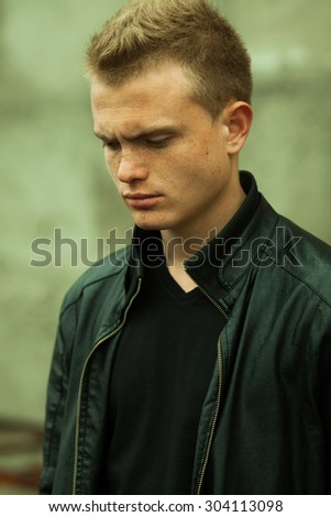 Stylish bully concept. Portrait of brutal young man with short wet hair wearing black jacket and posing over urban background. Hipster style. Close up. Outdoor shot