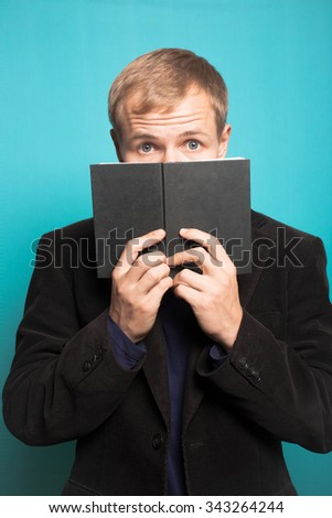 stylish business man hiding behind the book, with a beard and mustache, office style studio shot on isolated blue background - stock photo