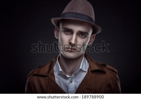 Stylish businessman in a raincoat and hat. Business portrait. Office worker