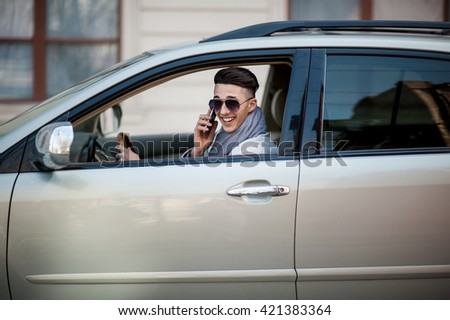 Stylish businessman in the window of his own luxury car. Cheerful and joyful. - stock photo