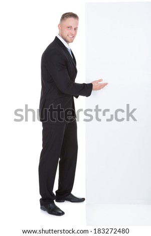 Stylish businessman pointing to a blank white sign that he is standing next to with a friendly smile as he draws your attention to the copyspace - stock photo