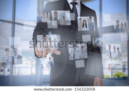 Stylish businessman presenting coworkers pictures on digital interface - stock photo