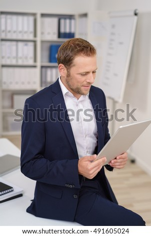 Stylish businessman reading a handheld document as he perches on the edge of a table in the office, close up high angle view