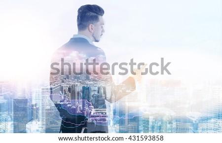 Stylish businessman using smart phone on New York city background. Double exposure - stock photo