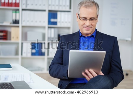 Stylish businessman working on a handheld tablet computer with a pensive smile as he sits on a chair at hid desk in the office - stock photo